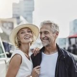 Elderly couple smiling with city in the background.